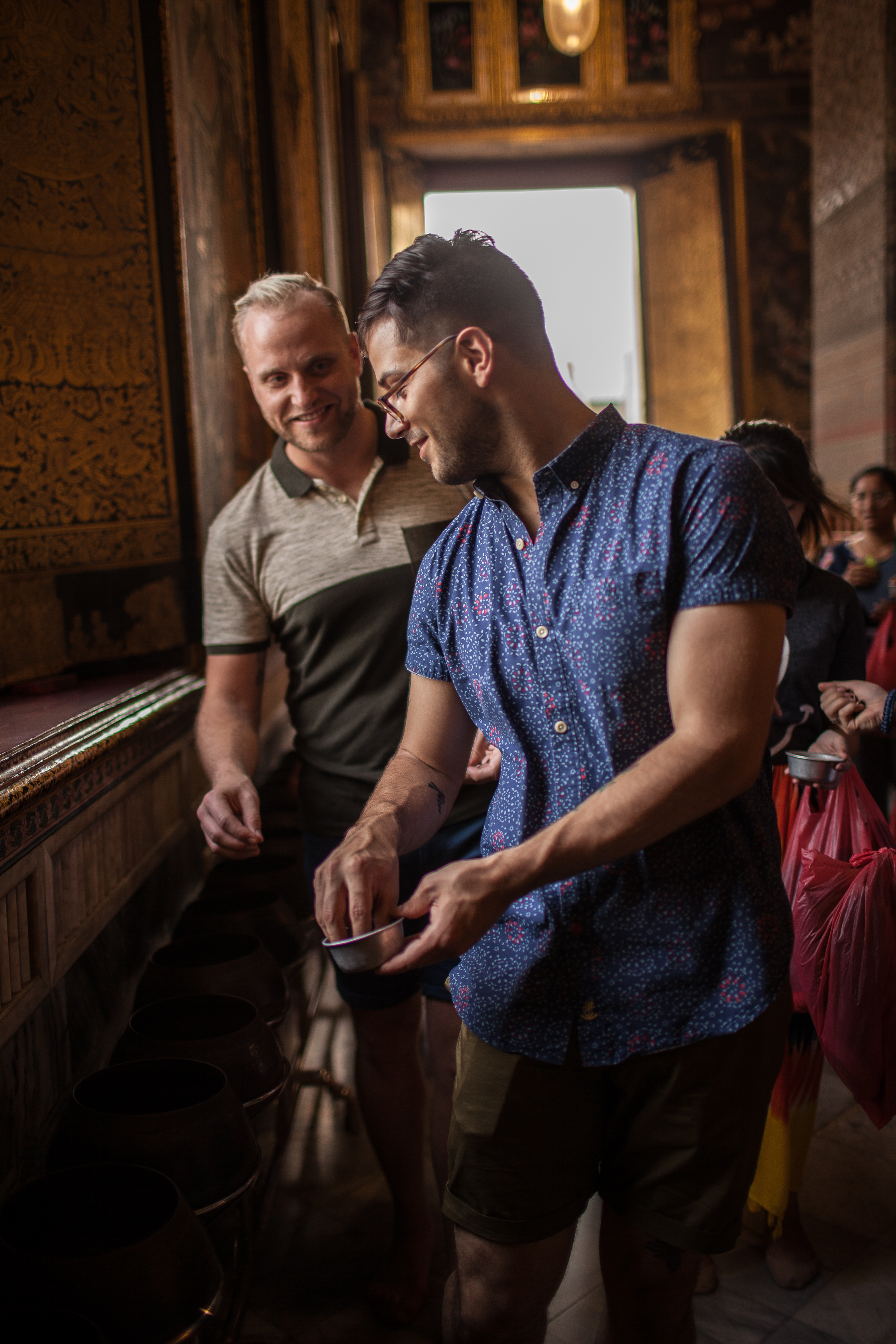 Giving coins at Temple of reclining buddha